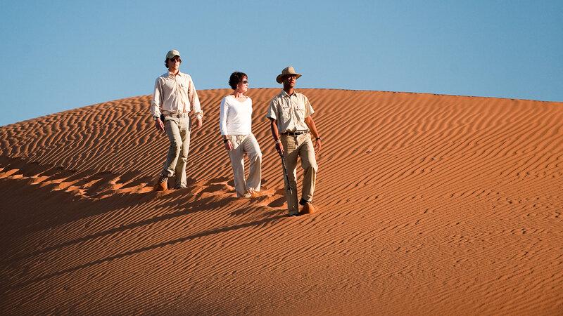 Namibië-algemeen-koppel wandelt in de duinen