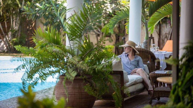 Tanzania-Arusha-Coffee-vrouw-hoed-kijkend-naar-zwembad