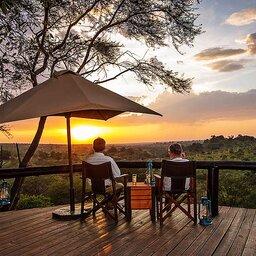 Tanzania-Serengeti NP-Elewana Collection Migration Camp-deck-koppel-zonsondergang-Niels-van-Gijn